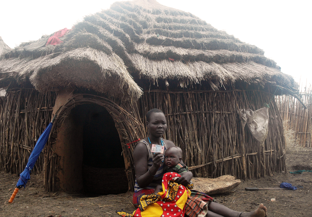 Photo of a woman with a chiild in her arm sits in front of a thatched hut in Uganda showing an ID card