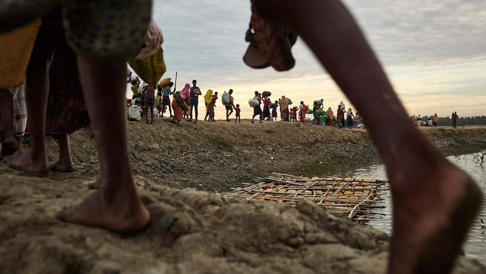 Rohingya refugees walk on an embankment of the Naf River, which separates Myanmar and Bangladesh, in November 2017.