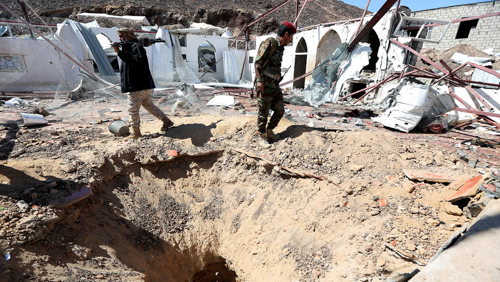 Government soldiers walk at the site of a missile attack on a military camp's mosque in Marib.