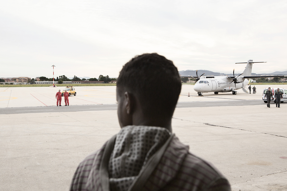 The back of a head in the foreground with a runway and planes in the background