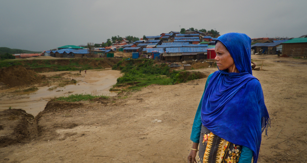 A woman in blue stands in front of a refugee camp looking to the side