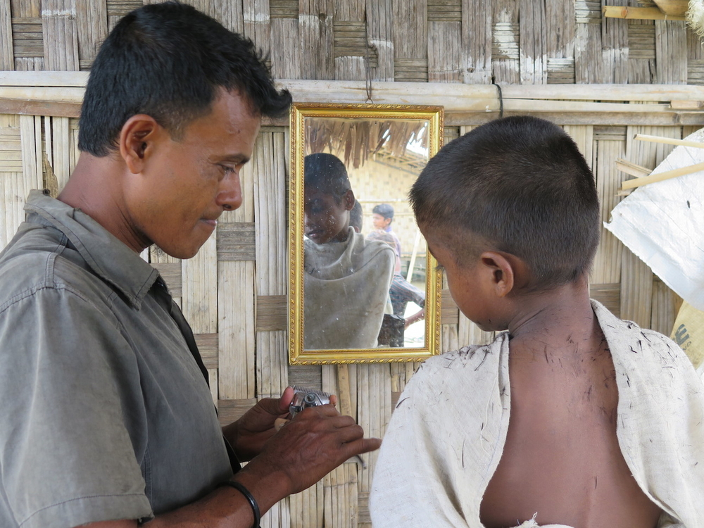 A Rohingya boy gets a haircut