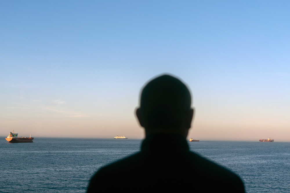 Photo of a silhouette of a man looking out at the Mediterranean Sea from a ferry to Spain