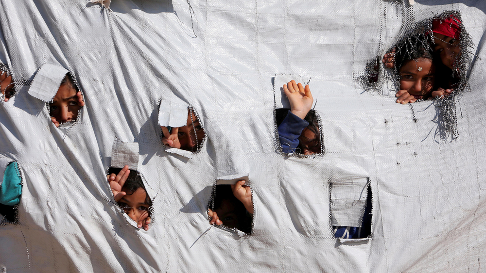 Children look through holes in a tent at the volatile al-Hol displacement camp, where nearly 70,000 people are in need of aid.