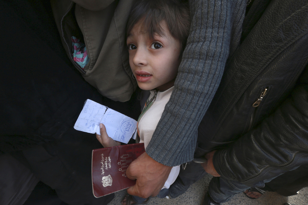 A boy carries identification papers while waiting in line to receive humanitarian aid in Douma, northeast of Damascus, 2014.