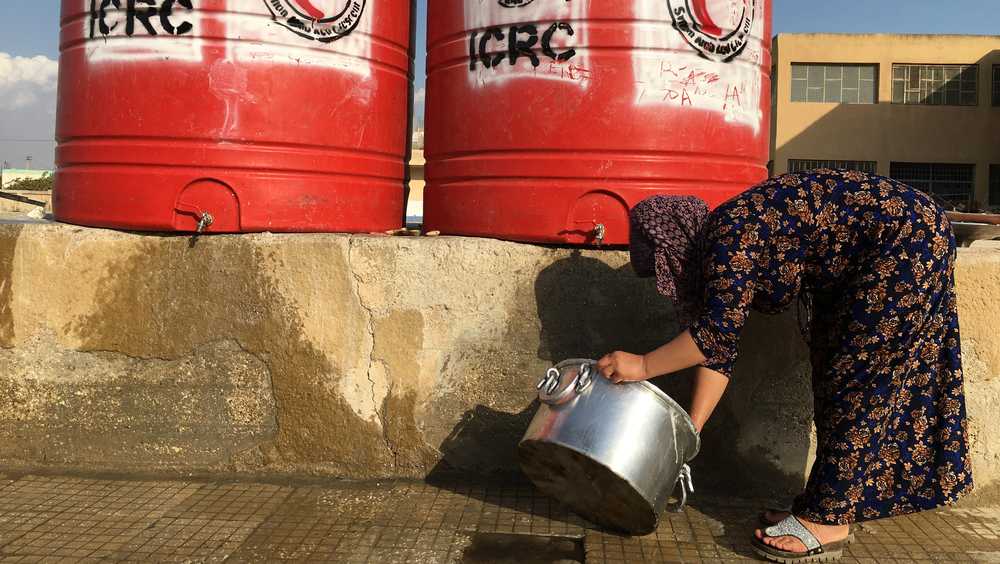 A displaced Syrian woman does the dishes in the courtyard of a school-turned-shelter in Hassakeh.