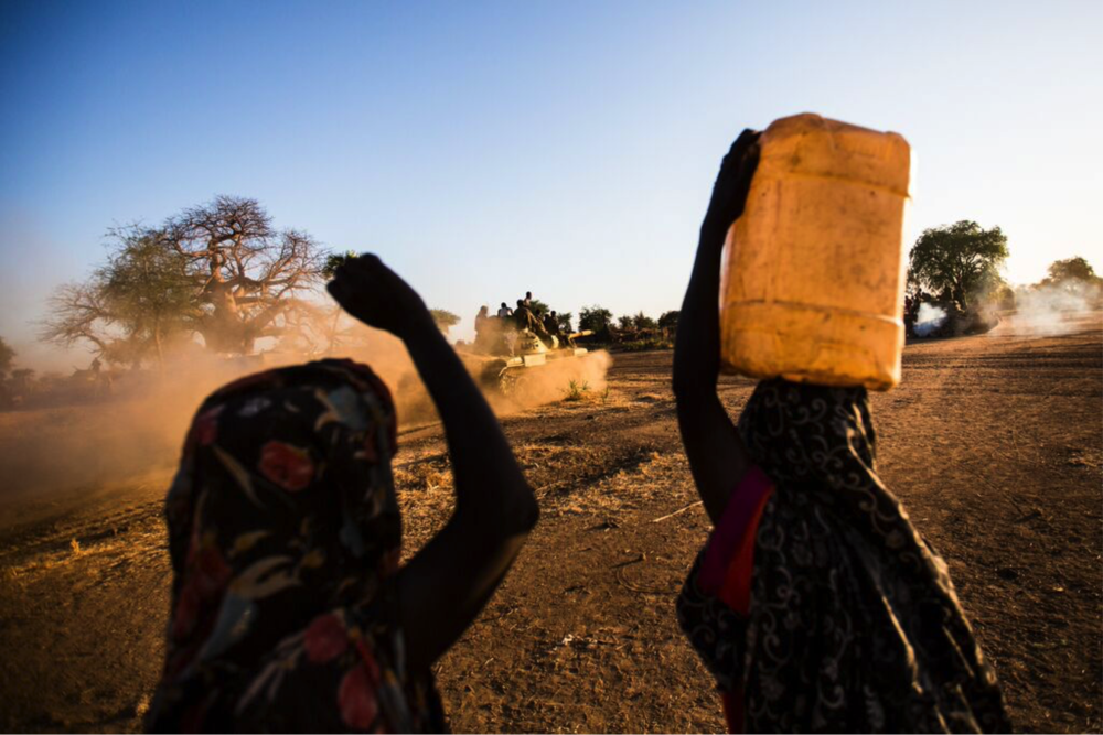 two women walk carrying water