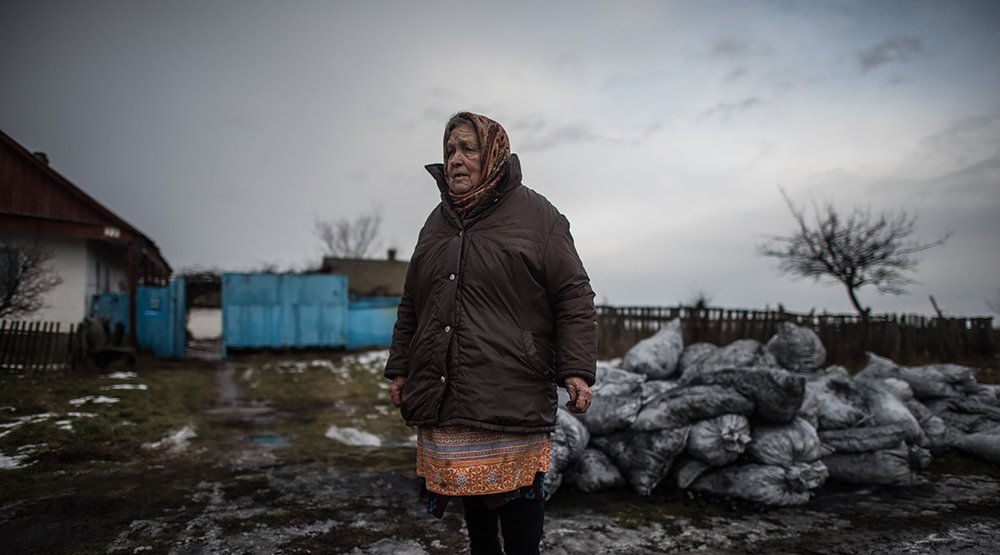 An elderly woman stands in the winter in Ukraine near the contact line of conflict.
