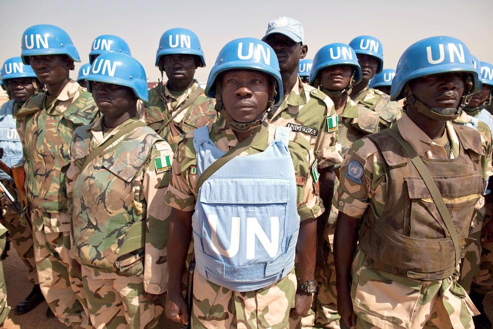 Photo of peacekeeper soldiers in a line wearing UN helmets in Darfur, Sudan.