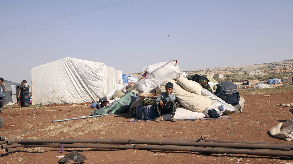 A child sits in a makeshift camp.