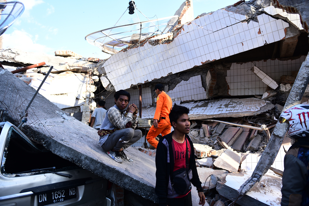 People sit on rubble of destroyed buildings and a car in Indonesia