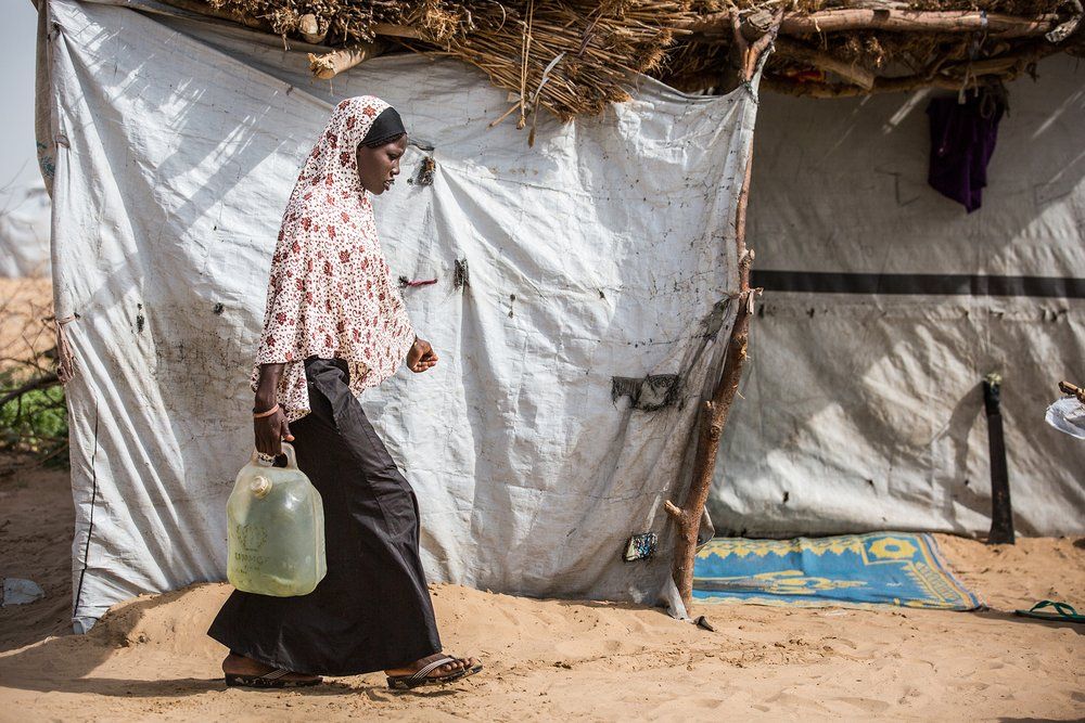 A woman walks in front of a temporary shelter with a water jug