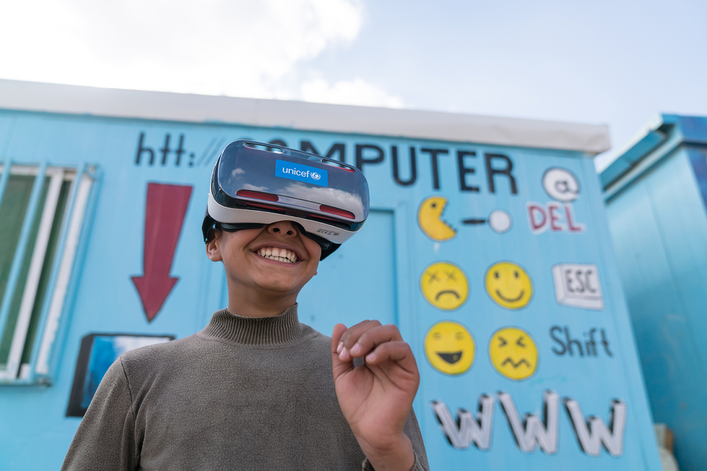 A boy with VR goggles on outside of a refugee camp for Syrians in Jordan.