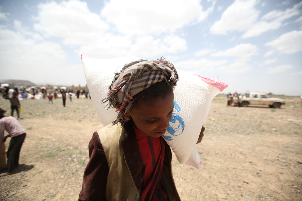 A boy carries food aid he received from the local charity, Mona Relief, on the outskirts of Sanaa, Yemen.